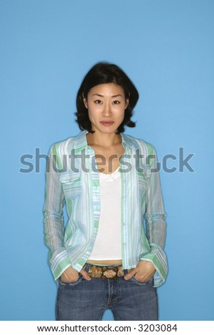 Half length portrait of pretty Asian mid adult woman  on blue background.