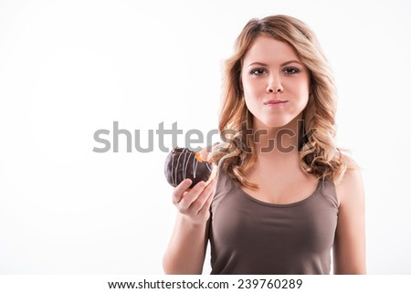 Half-length portrait of pretty smiling blonde woman biting a doughnut, weight loss concept, isolated on white background - stock photo
