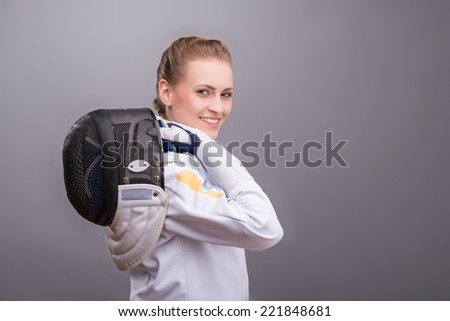 Half-length portrait of pretty smiling girl wearing fencing costume standing aside holding her fencing mask on her shoulder. Isolated on dark background - stock photo