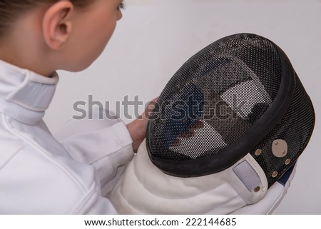 Half-length portrait of pretty young woman wearing white fencing costume sitting aside holding and looking at her black fencing mask in her hands. Isolated on white background - stock photo