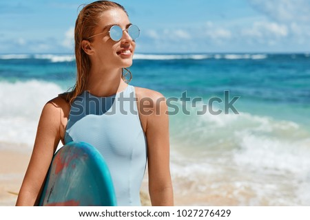 Half length portrait of satisfied happy wet woman being glad after active surfing training on ocean, prepares for competitions, carries surfboard, looks thoughtfully aside, poses against sea horizon