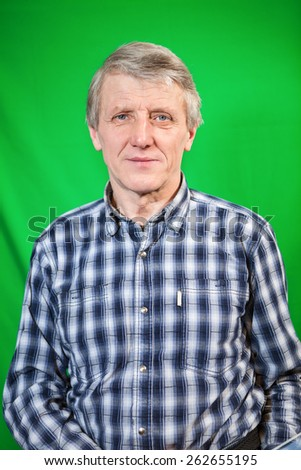 Half length portrait of senior Caucasian man, green background - stock photo