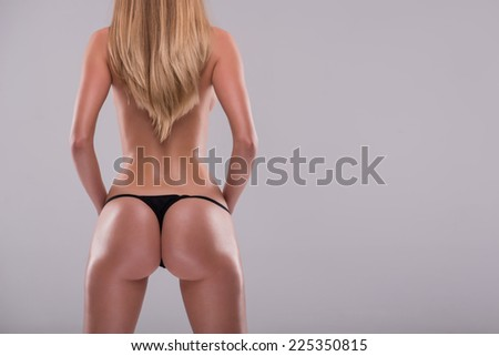 Half-length portrait of sexy beautiful blonde with great figure wearing black lingerie standing back showing the beauty of her wonderful body. Isolated on white background - stock photo