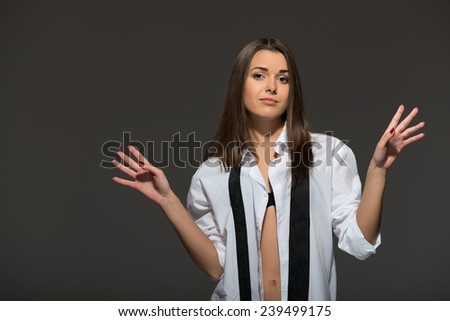 Half-length portrait of sexy young Caucasian brunette wearing men white shirt, tie undone and lingerie raining hands, provocative emotional look, isolated on grey background - stock photo
