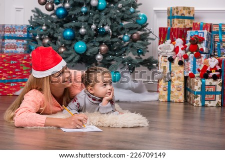 Half-length portrait of smiling fair-haired mom wearing red cap lying on the floor near the Christmas tree with her little cute daughter writing a letter for Santa Claus looking at someone very - stock photo
