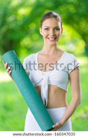 Half-length portrait of sportswoman keeping mat. Concept of healthy lifestyle and sports