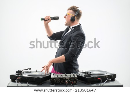 Half-length portrait of stylish emotional DJ in tuxedo spinning and dancing by the turntable with microphone isolated on white background, side view - stock photo
