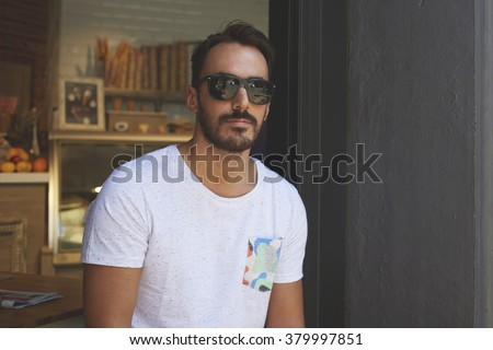 Half length portrait of stylish young business owner in dark sunglasses posing near own grocery store, confident handsome rich male resting near bakery during recreation time in warm summer season - stock photo