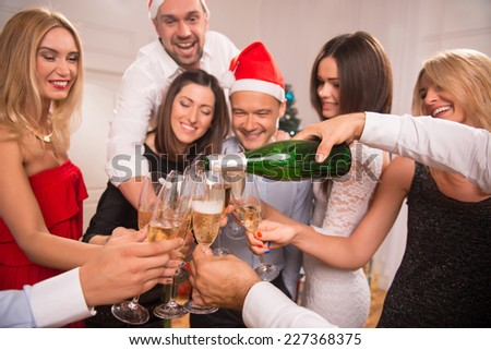 Half-length portrait of the company of happy young friends standing in a circle pouring the champagne greeting each other with the New Year - stock photo