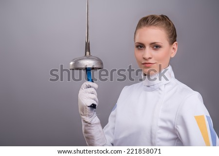 Half-length portrait of the fair-haired pretty girl wearing white fencing costume standing aside presenting us her sward. Isolated on grey background - stock photo