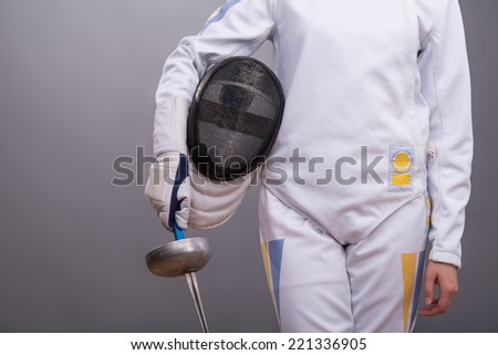 Half-length portrait of the girl wearing fencing costume holding the rapier and fencing mask in one hand. Isolated on dark background - stock photo
