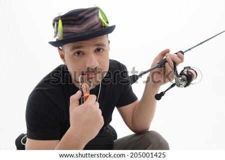 Half-length portrait of thoughtful fisherman holding in one hand the bait and in another fishing rod. Isolated on white background - stock photo
