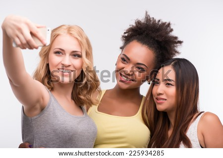 Half-length portrait of three beautiful smiling girls wearing colorful T-shirts making self-photo. Isolated on white background - stock photo