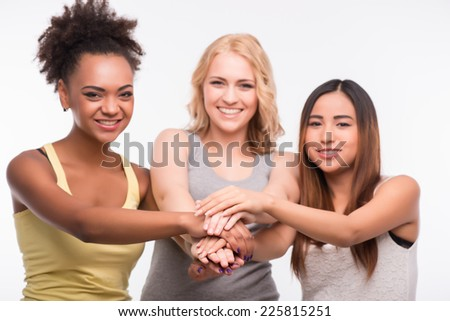 Half-length portrait of three beautiful smiling girls wearing T-shirts and jeans putting their hands together. Isolated on white background - stock photo