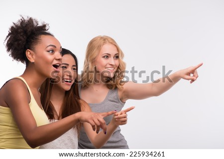 Half-length portrait of three young lovely girls wearing colorful T-shirt looking and pointing at someone with surprise. Isolated on white background - stock photo