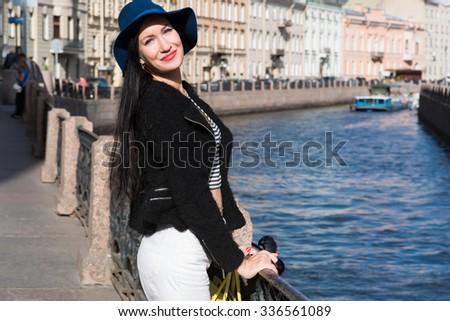 Half length portrait of trendy young woman standing near the river while enjoying strolling in warm spring day, beautiful and gorgeous female posing in urban setting with copy space background - stock photo