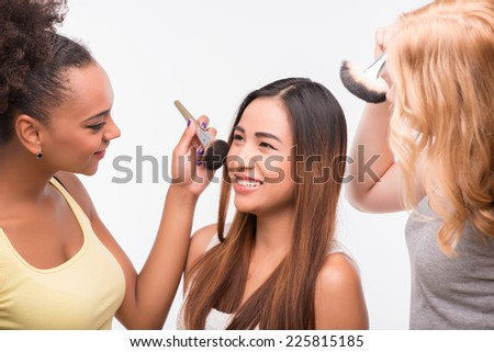 Half-length portrait of two beautiful girls doing make up their best friend sitting and smiling. Isolated on white background - stock photo