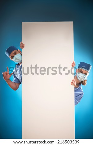 Half-length portrait of two doctors wearing blue medical uniform and masks looking out of the huge poster for copy place. Isolated on blue background - stock photo