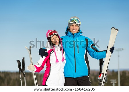 Half-length portrait of two embracing downhill skiers with skis in hands - stock photo