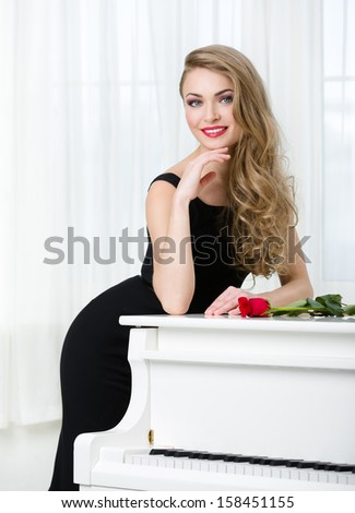 Half-length portrait of woman in black dress standing near the piano with red rose on it. Concept of music and arts - stock photo