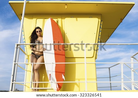 Half length portrait of women with sexy perfect body standing on lifeguard house with surfboard with copy space for your brand, young surfer female in bikini relaxing after swimming in ocean in summer
