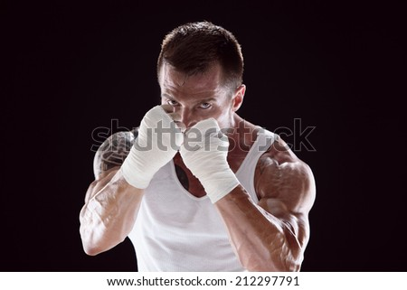 Half-length portrait of working out fighter with hands wrapped with bandage, isolated on black - stock photo