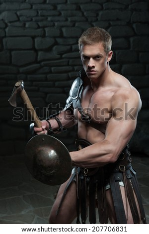 Half length portrait of young attractive warrior gladiator with muscular body holding shield and axe, defending on dark background. Concept of masculine power, strength