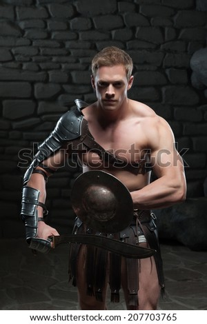 Half length portrait of young attractive warrior gladiator with muscular body posing with shield and sword on dark background. Concept of masculine power, strength.