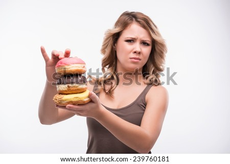 Half-length portrait of young attractive woman rejecting doughnuts isolated on white background, selected focus, diet concept - stock photo