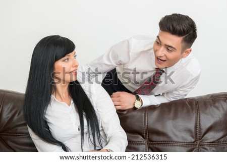 Half-length Portrait of young businessman  and his pretty colleague woman smiling to each other in office interior