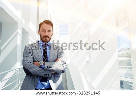 Half length portrait of young confident man manager standing with crossed arms in hall of his corporation, prosperous male leadership dressed in elegant luxury clothes relaxing after business meeting  - stock photo