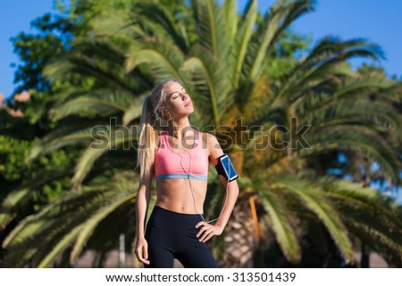 Half length portrait of young female jogger closed her eyes enjoying the sun and rest after morning run, fit caucasian woman listening to music in headphones while taking break after workout outdoors - stock photo