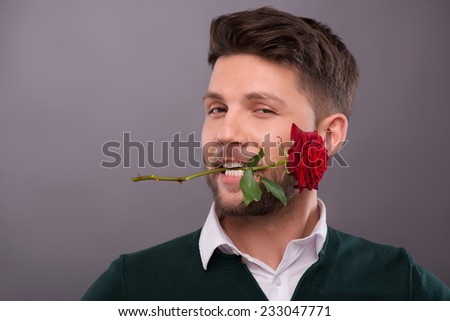 Half-length portrait of young handsome man wearing green sweater and white shirt keeping wonderful red rose in his mouth. Isolated on grey background - stock photo