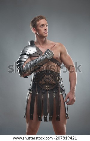 Half length portrait of young handsome muscular man gladiator in armour pointing up isolated over grey background - stock photo