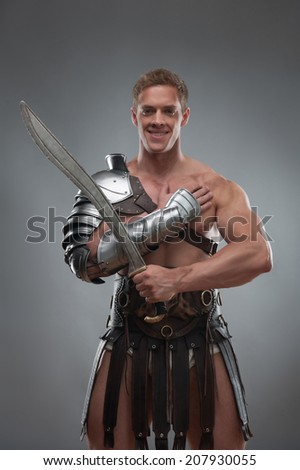 Half length portrait of young handsome muscular man gladiator in armour posing with his arms crossed, smiling and holding sword isolated over grey background