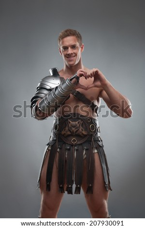Half length portrait of young handsome muscular man gladiator in armour showing sign of heart, heart shape gesture, isolated over grey background - stock photo