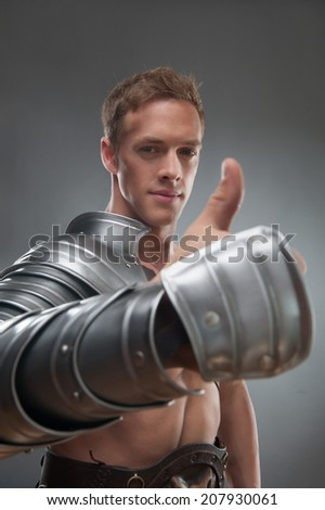 Half length portrait of young handsome muscular smiling man gladiator in armour showing ok sign with thumbs up, selective focus, isolated over grey background - stock photo