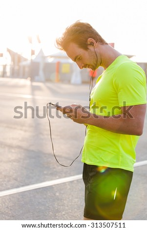 Half length portrait of young male athlete view web pages on his smart phone while resting after a fitness workout outdoors, handsome man listening to music on headphones on smart phone while resting - stock photo