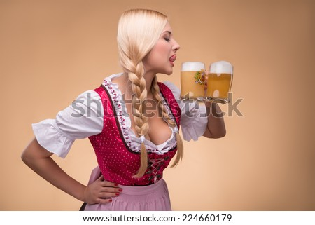 Half-length portrait of young sexy smiling blonde wearing pink dirndl and white blouse standing aside going to drink her favorite beer. Isolated on dark background - stock photo