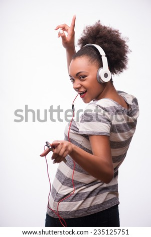 Half-length portrait of young smiling African girl wearing striped T-shirt standing back holding mp3 player in her hand and great earphones on the head looking at us. Isolated on white background - stock photo