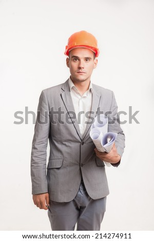 Half-length portrait of young smiling handsome architect engineer in orange helmet posing with blueprints looking at camera isolated on white background, copyspace - stock photo
