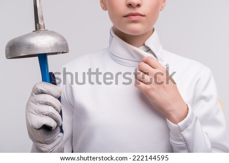 Half-length portrait the woman wearing white fencing costume holding a sword in one hand touching the collar. Isolated on white background - stock photo