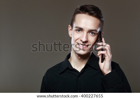 half lenth portrait of attractive young man talking on the cellphone isolated on the dark background looking at camera