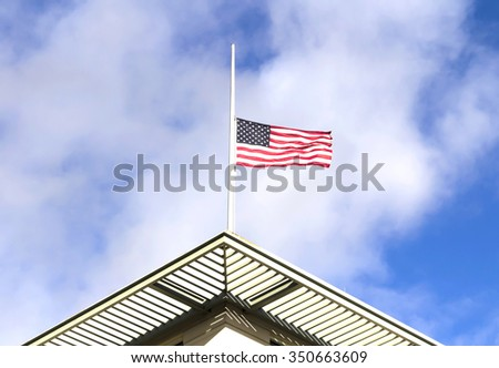 Half mast American flag,  on a cloudy day - stock photo