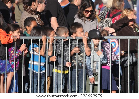 HALF MOON BAY, CA - OCTOBER 2015 - Children at the Half Moon Bay Pumpkin Festival clamor to see which giant pumpkin will win at the 45th annual Pumpkin Weigh-Off contest in Half Moon Bay, California.  - stock photo