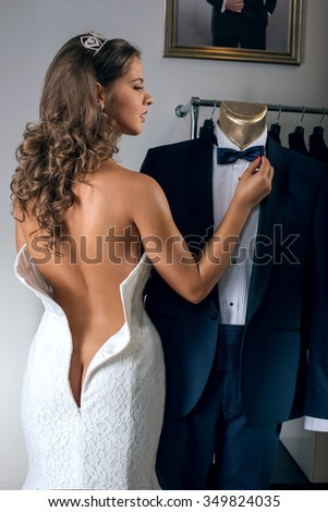 Half naked bride  in wedding dress looks at the groom's suit in the salon - stock photo