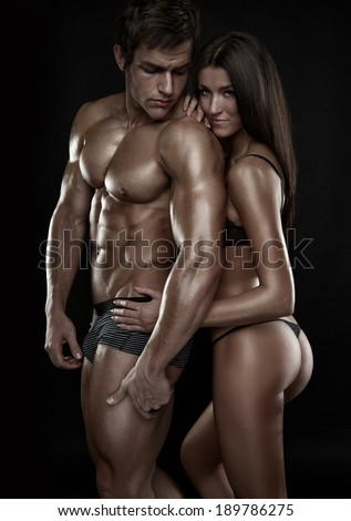 half-naked sexy couple, beautiful woman holding a muscular man isolated on a black background - stock photo