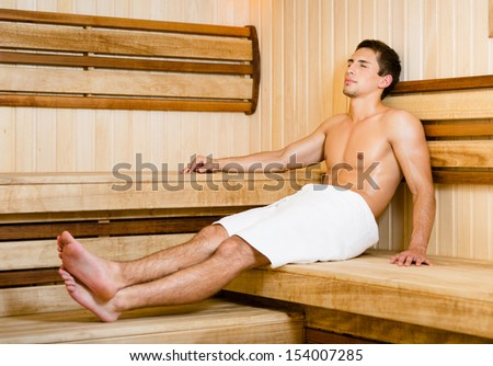 Half-naked young man relaxing in sauna. Concept of self-care, health and relaxation - stock photo