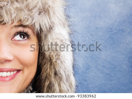 Half of a beautiful smiling woman's face, winter portrait against a blue and white background. - stock photo