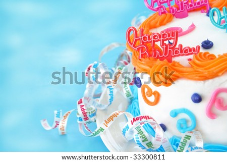 Half of a birthday cake with the words happy birthday as a decoration on top of the cake.  Ribbons are surrounding the bottom of the cake that say Happy Birthday.  Room for text. - stock photo
